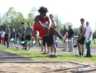 Spectators watch Derby High School's Zerion Montgomery jump more than 21 feet in the long jump during the three school track meet between Wilby, Woodland, and Derby at Woodland Regional High School on Tuesday afternoon. Emily J. Reynolds. Republican-American