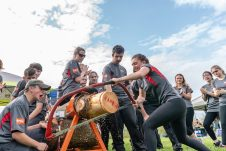 Wamogo senior Melissa Demetri, left, while being cheered on by her teammates speedily uses a bow saw to cut through a log, during a Timber team competition between Wamogo and Woodland at Woodland Regional High School in Beacon Falls on Friday. Bill Shettle Republican-American
