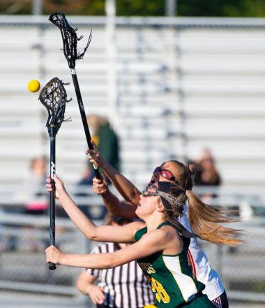 Holy Cross' Kylie O'Brien (28) gets to the ball before Watertown's Hannah Mehlin (7) during their lacrosse match Wednesday at Watertown High School. Jim Shannon Republican American