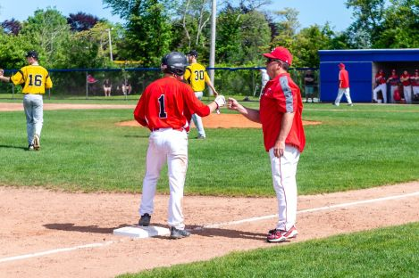 Cheshire's Paul Villecco #1 gets a fist pump from his head coach Mike Lussier, after hitting for a triple, during the SCC championship game between Amity and Cheshire at Piurek Field in West Haven on Saturday. Bill Shettle Republican-American