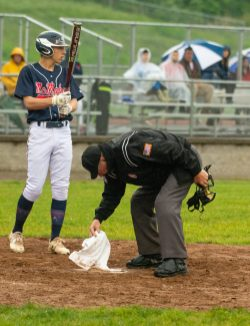 Home plate umpire Elmer Deschaine uses a towel to wipe off home plate as the rain fell during Naugatuck's Class LL first round tournament game against Brien McMahon Tuesday at Naugatuck High School. Jim Shannon Republican American