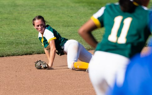 Holy Cross' Allie Brown (1) checks the runner after making a diving catch during their Class S semi-final game with Coginchaug Monday at West Haven High School. Jim Shannon Republican American