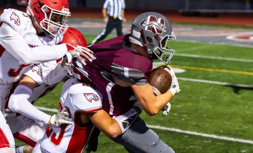 Naugatuck's Jeff Schebell (24) gets ridden out of bounds by Wolcott's Jack Byrnes (5), Jacob Talbot (3) and Kyle Hensel (25), but not before getting a first down, during their season opening game Friday at Naugatuck High School. Jim Shannon Republican-American