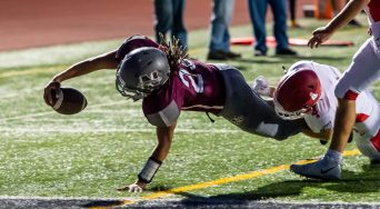 Naugatuck's (29) dives in for a two-point conversion after getting past Wolcott's Nicholas LaFountain during their season opening game against Wolcott Friday at Naugatuck High School. Jim Shannon Republican-American