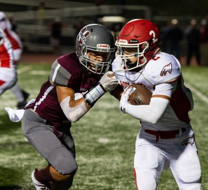 Wolcott's Joe Fontano (2) gets brought down for a loss by Naugatuck's Isaiah Williams (1) during their season opening game Friday at Naugatuck High School. Jim Shannon Republican-American