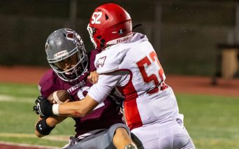 Wolcott's Naugatuck's Jay Mezzo (12) is dropped for a huge loss by Wolcott defender on a bad snap during their season opening game Friday at Naugatuck High School. Jim Shannon Republican-American