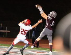 Naugatuck's Connor Maxwell (34) pulls down a touchdown pass in front of Wolcott's Ian Helbig (26) during their season opening game Friday at Naugatuck High School. Jim Shannon Republican-American