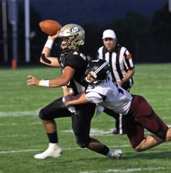 Woodland's Tyler Bulinski (12) is called for intentional grounding the ball as he tries to evade Torrington's Logan Kovall (7) during NVL football action at Woodland High School Friday night. Michael Kabelka / Republican-American