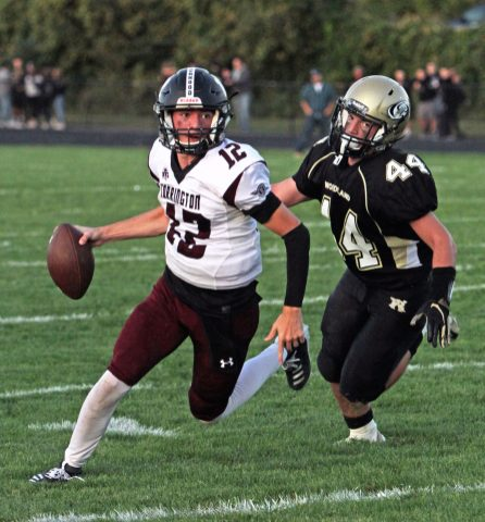 Torrington's Conrad Avallone scrambles away from Woodland's Benjamin Brooks (44) during NVL football action at Woodland High School Friday night. Michael Kabelka / Republican-American