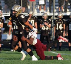 Woodland's Jason Palmieri (8) breaks a tackle from Torrington's Kye Smith (27) as the Woodland bench looks on during NVL football action at Woodland High School Friday night. Michael Kabelka / Republican-American