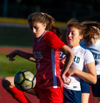 Wolcott's Jenna Tracey (5) holds off Oxford's Franchesca Guglielmo(22) as she gets control of the ball during their game Tuesday at Wolcott High School Jim Shannon Republican-American