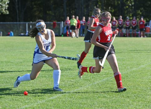 Lewis Mills High School's Hope Guillemette drives the ball up the field ahead of Wamogo High School's Sydney Marhefsky during the girls varsity field hockey game at Lewis Mills on Wednesday afternoon. Emily J. Tilley. Republican-American