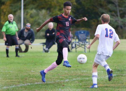 #11 Noah Arigoni of Wamogo High kicks ball past #12 Owen Hale of Nonnewaug High during soccer action in Litchfield Monday. Steven Valenti Republican-American