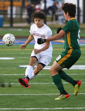 #1 Saul Pujols of Naugatuck High clears a ball past #9 Luciano D'Amelio of Holy Cross High during NVL Soccer action in Waterbury Monday. Steven Valenti Republican-American