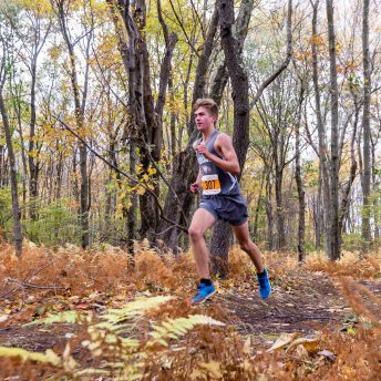 Nicholas Bendtsen of Wolcott runs all alone in the woods in first place, during the Boys NVL Cross Country Championships at Veterans Park on Friday. Bill Shettle Republican-American
