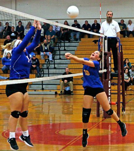 Seymour's Jacey Cosciello returns a volley as Saint Paul's Megan Fortier defends during the NVL semi-final match at Torrington High School Monday night.. Michael Kabelka / Republican-American