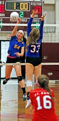 Seymour's Faith Rousseaur returns a ball as Saint Paul Kelsi Blatchley (33) and Grace Carabetta defend during the NVL semi-final match at Torrington High School Monday night.. Michael Kabelka / Republican-American