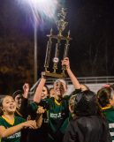 Holy Cross' Alyssa Hebb (16) raises the trophy high celebrating with her teammates after Holy Cross came from two goals down to beat Watertown 3-2, during the NVL Girls Soccer final between Holy Cross and Watertown at Municipal Stadium on Thursday. Bill Shettle Republican-American