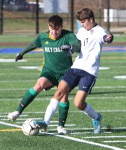 #14 Thomas Pompei of Holy Cross gets the ball past #17 Luke Lourenco of Bolton High during the second round of Class S boys soccer tournament at Municipal Stadium in Waterbury Wednesday. Steven Valenti Republican-American