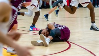 Naugatuck's Avery Hinnant (4) collapses to the floor with a cramp during their key NVL match-up with Sacred Heart Friday at Alumni Hall at Sacred Heart High School. Jim Shannon Republican-American
