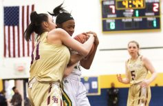 #31 Emily Ronalter of Sacred Heart and #23 Carla Howard of Holy Cross get wrapped up in the jump ball during the girls NVL Tournament semi-final in Waterbury Monday. Steven Valenti Republican-American