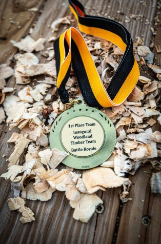 A medal for the first place team sits on a pile of wood chips following the Woodland Timber Team Battle Royal Friday at Woodland Regional High School. Jim Shannon Republican-American