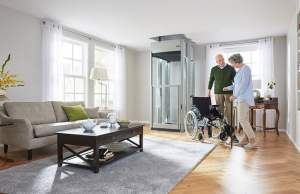 Couple with wheelchair near home lift in living room