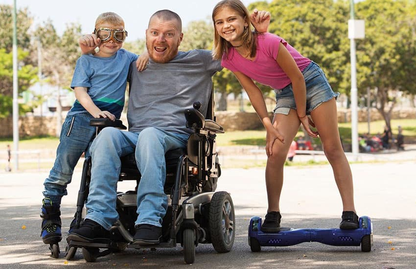 Disabled man in powerchair with two children