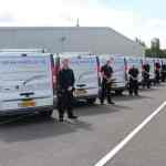 Prism Medical UK team standing outside vans