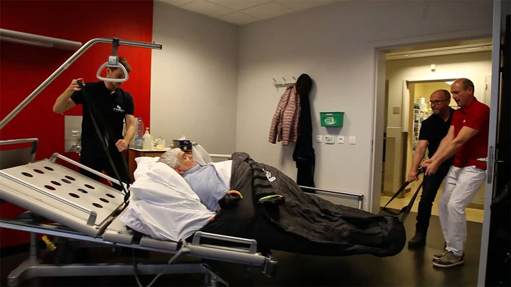 S-CAPEPOD in use, with bariatric patient carried by three healthcare professionals