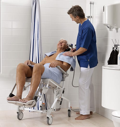 Man sat in Etac Swift Mobil Tilt Shower Chair with carer
