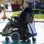 Man in powered wheelchair crossing the road