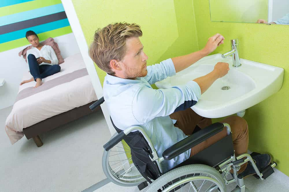 Disabled man using bathroom in accessible home