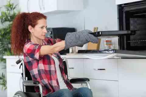 Wheelchair user in accessible housing kitchen