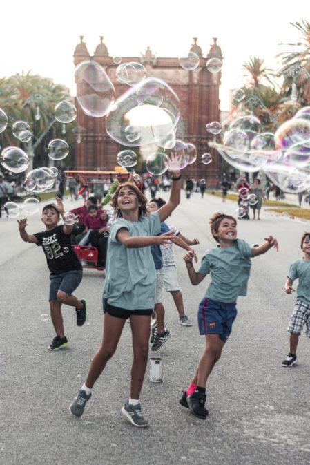 kinderen spelen op straat met zeepbellen