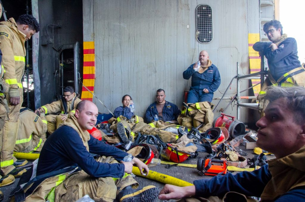 SAN DIEGO (July 14, 2020) Sailors rest after battling a fire aboard the amphibious assault ship USS Bonhomme Richard (LHD 6). On the morning of July 12, a fire was called away aboard the ship while it was moored pierside at Naval Base San Diego. Base and shipboard firefighters responded to the fire. Bonhomme Richard is going through a maintenance availability, which began in 2018.