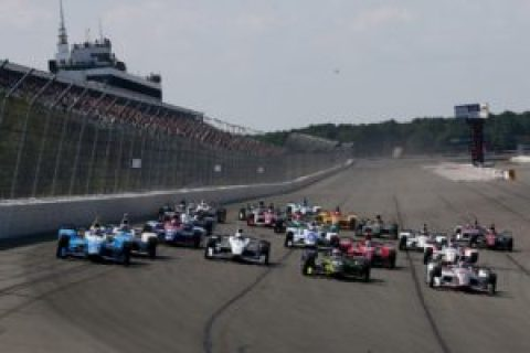 A field of IndyCars about to enter turn 1 at Pocono Raceway