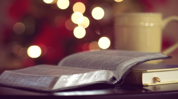 Bible in foreground with out-of-focus Christmas tree in background