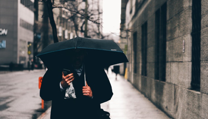 man walking on sidewalk with umbrella