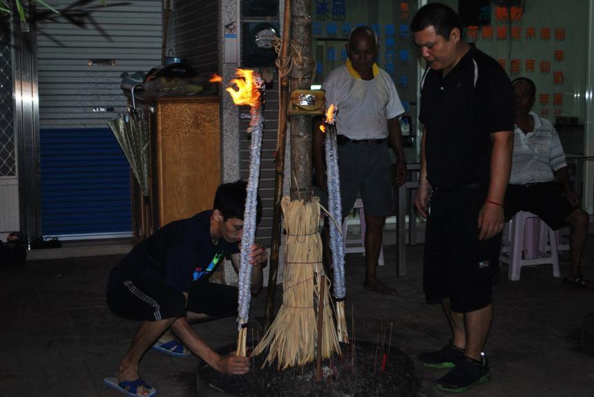 廟方人員將引自放水燈岸邊金紙火的火把安置於燈篙下。