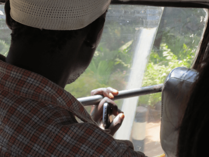 A person holding a phone while travelling on public transportation in Nairobi, Kenya (photo taken by the author during field research, © 2013 Michael Waltinger)