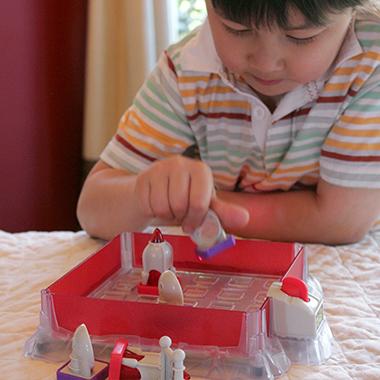 Child plays Laser Maze while thinking
