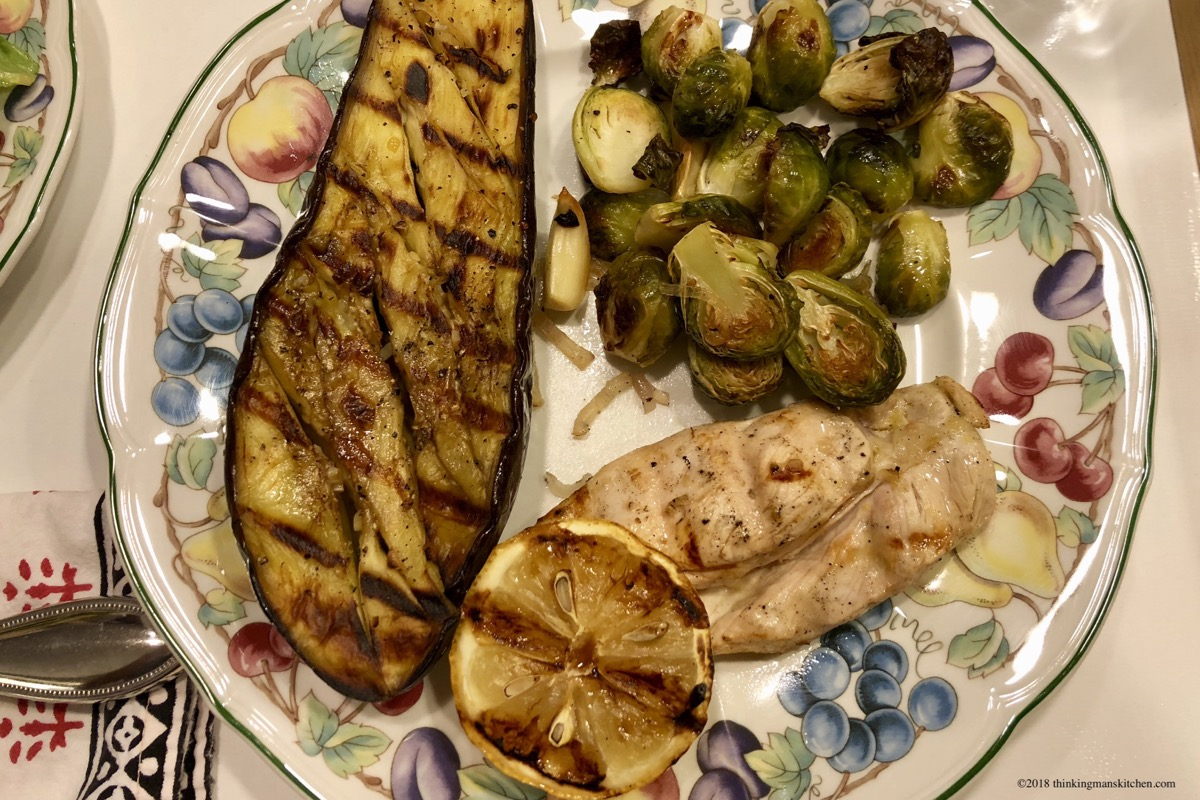 Plated dinner of chicken, eggplant, brussels sprouts and lemon