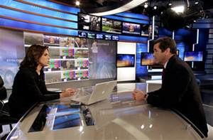 """CNN's Soledad O'Brien, left, and Miles O'Brien rehearse with the network's """"news wall"""" in the background."""