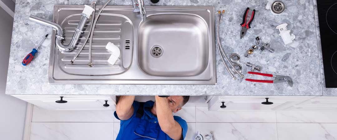 Repairman under a sink working on a garbage disposal