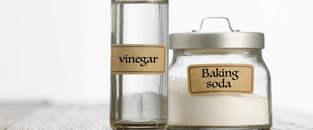 A jar of baking soda and a bottle of vinegar