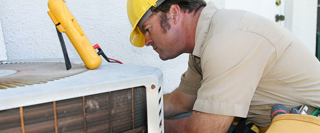 AC repairman working on outside unit