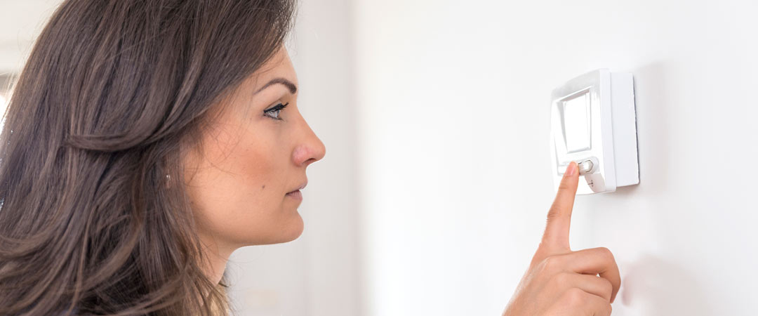 Lady adjusting ac thermostat on wall