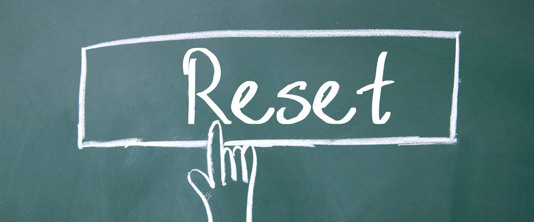 Chalk board drawing of a hand pointing to a reset button