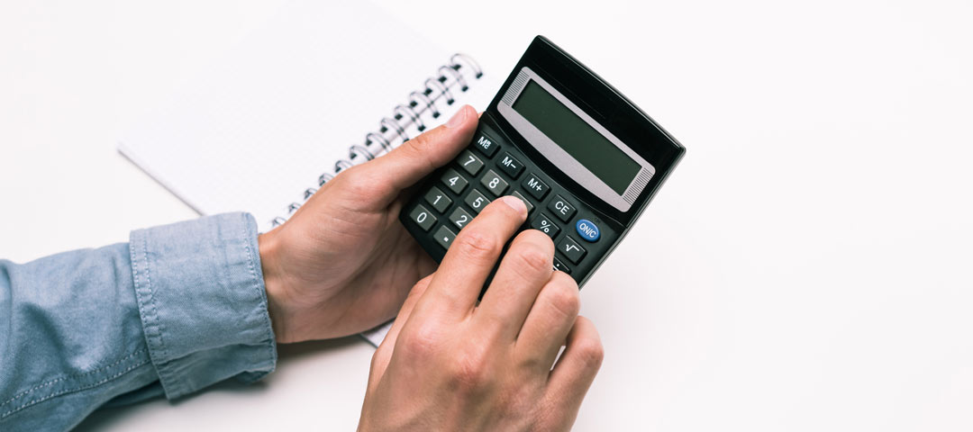 Man holding calculator with notebook in the background